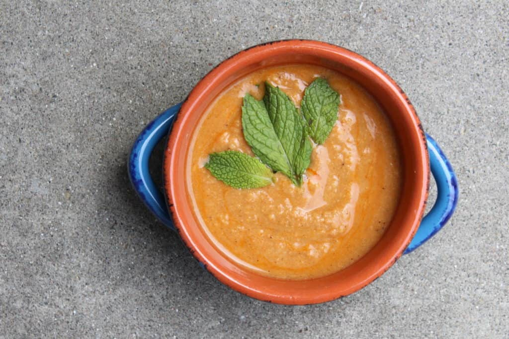 Overhead view of Creamy Chickpea stew in an orange and blue bowl on concrete