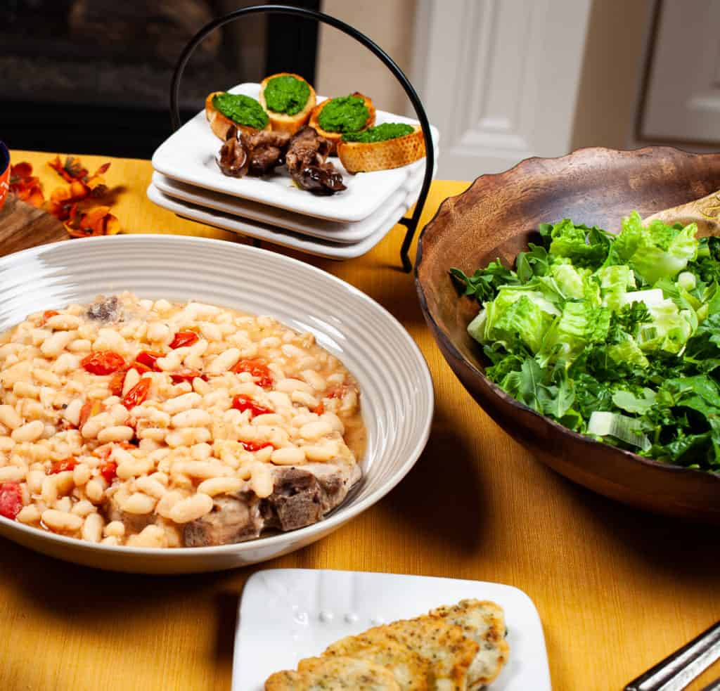 Table setting with fagioli soup, appetizers, and salad