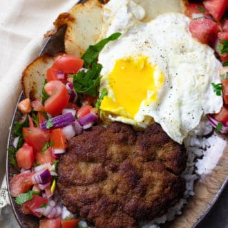 Bolivian Silpancho made with rice, a pan-fried burger, salsa, potatoes, and an egg