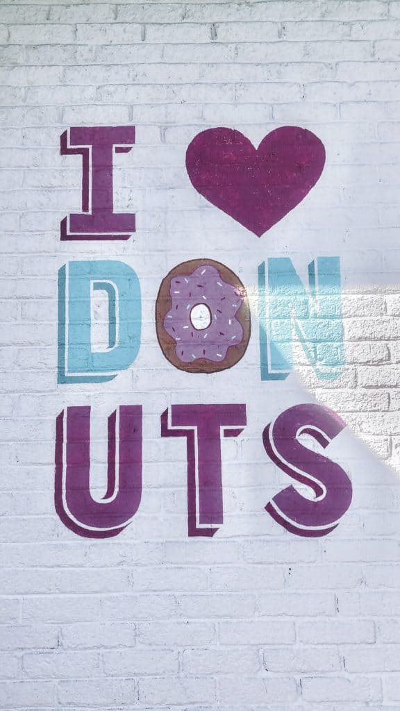 The I Love Donuts mural outside of Five Daughters Bakery