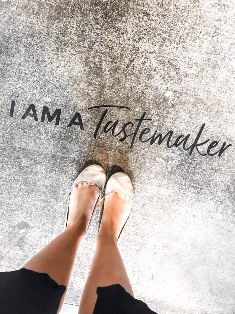 "photo of shoes in front of a sign that says ""I am a tastemaker"""