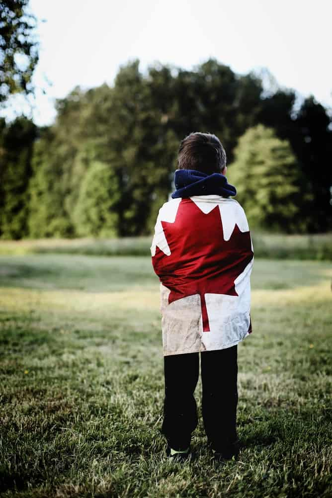 Canadian kid with flag wrapped around his back