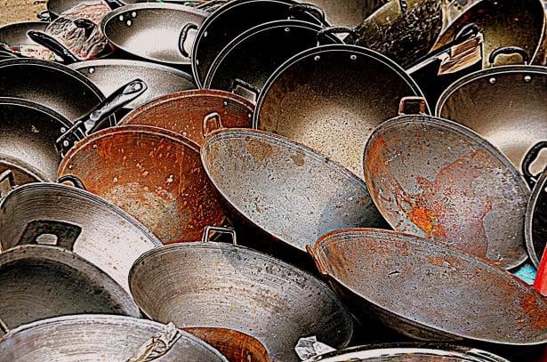 rusty woks in a pile