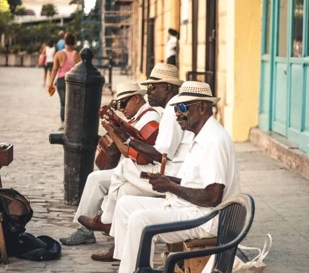 3 men playing instruments in the street