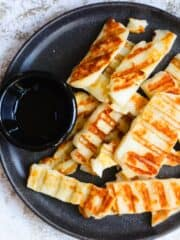 Grilled halloumi with bowl of honey