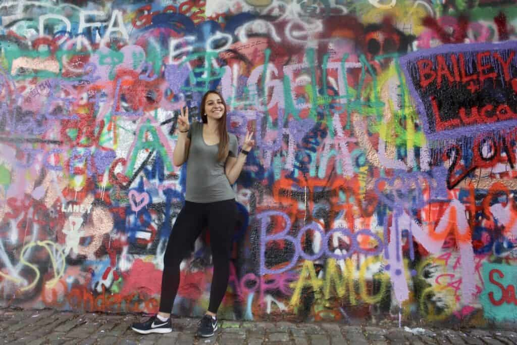 Alexandria posing in front of the John Lennon wall in Czech Republic