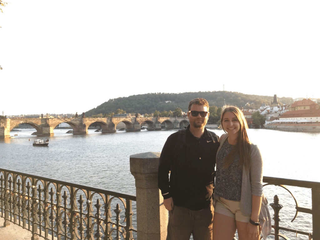 Alexandria and Tyler posing in front of a bridge in Prague