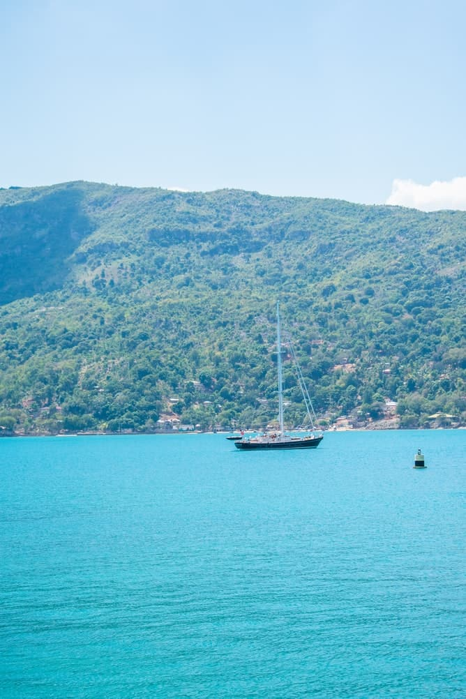 Blue water in Haiti with a sailboat