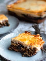 Moussaka recipe with a fork and a tray behind it
