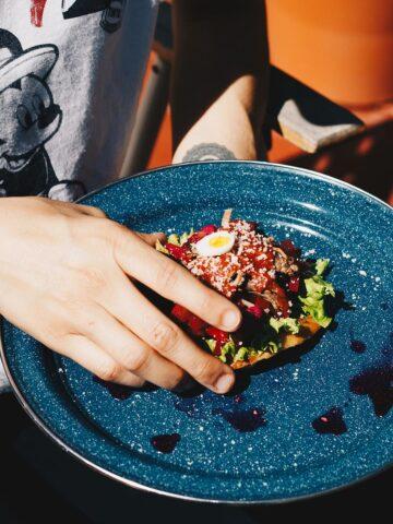 Guatemalan Food: Hand picking up a Tostada