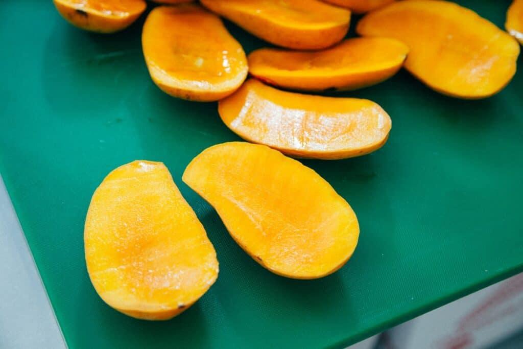 Jamaican Food: Mangos, sliced on a green board
