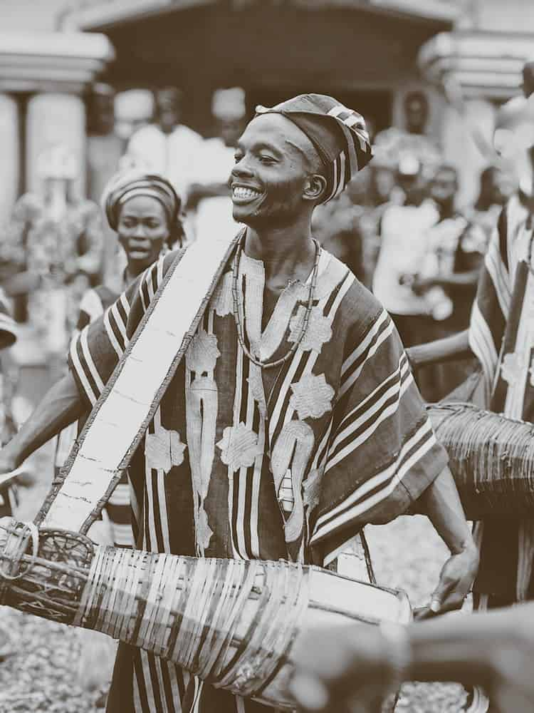 Black and white photo of smiling Nigerian drummer in traditional costume