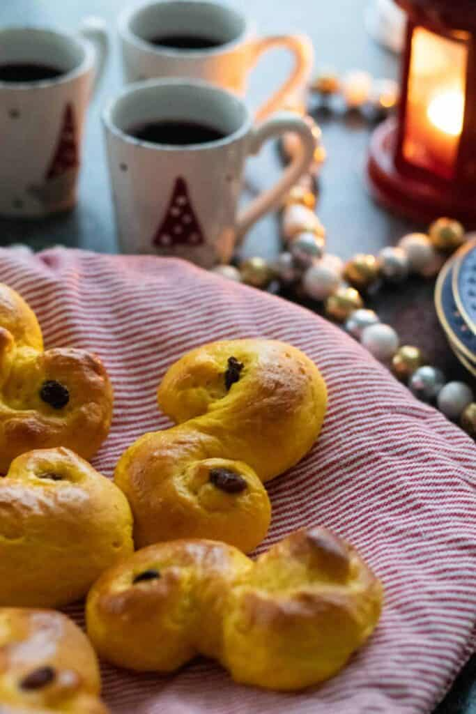 Swedish Food: Lussekatter (Saffron Buns) with Christmas decorations, like mugs, candles, etc
