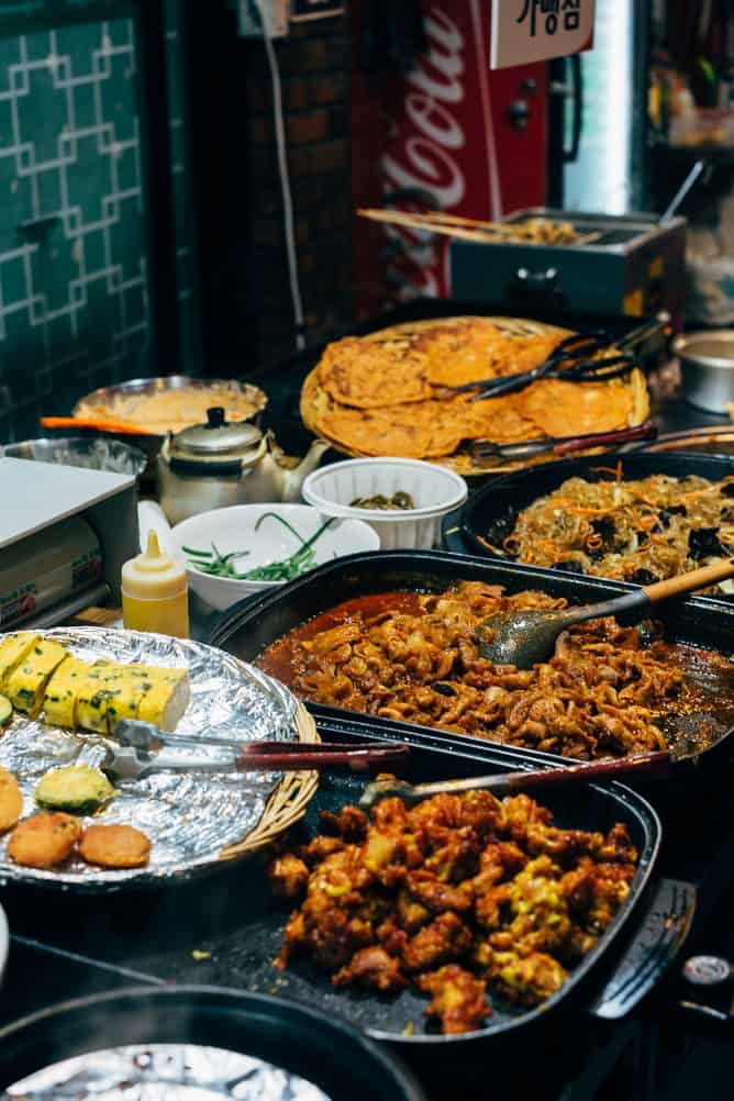 An array of Korean street food in serving trays with serving spoons