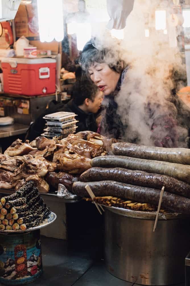A meat counter in Korea with a woman cooking behind smoke