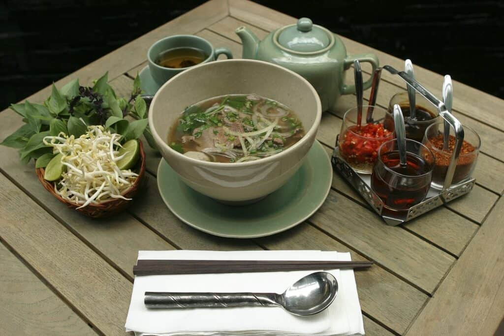 Vietnamese food: Beef Pho with a bowl, utensils, vegetables, and sauces