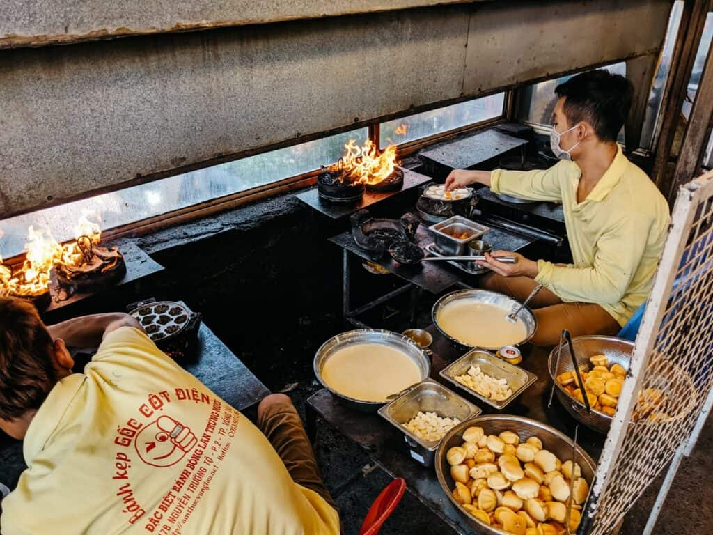 A restaurant setting in Vietnam with fires and bowls of food