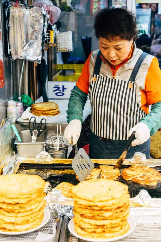 A woman cooking Korean street food in a striped apron