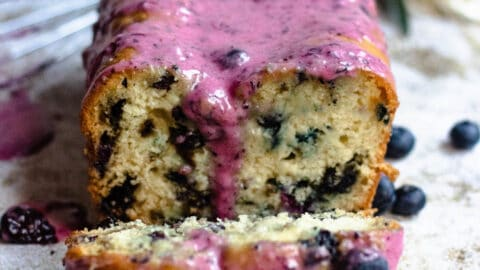 Blueberry bread loaf from the front with purple glaze