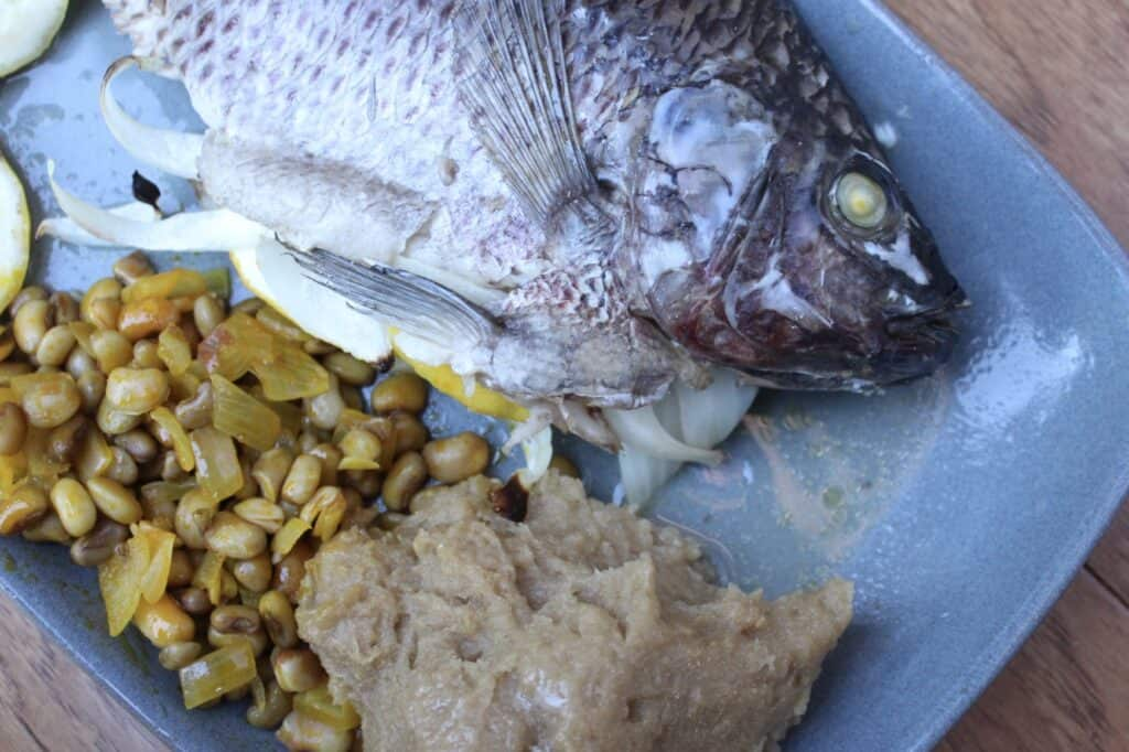 overhead view of a tilapia with eyes on a plate with funje and beans