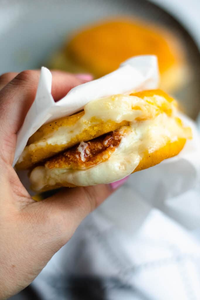 Hand holding two arepas stuffed with cheese