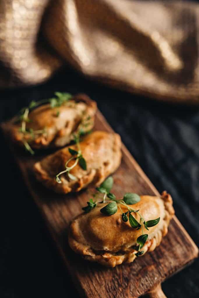 Dark photo of a wooden plank with baked pierogies and green herbs