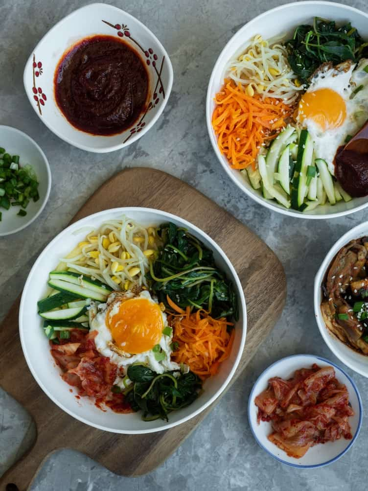 Overhead shots of bimbimbap with sauces, vegetables, and eggs