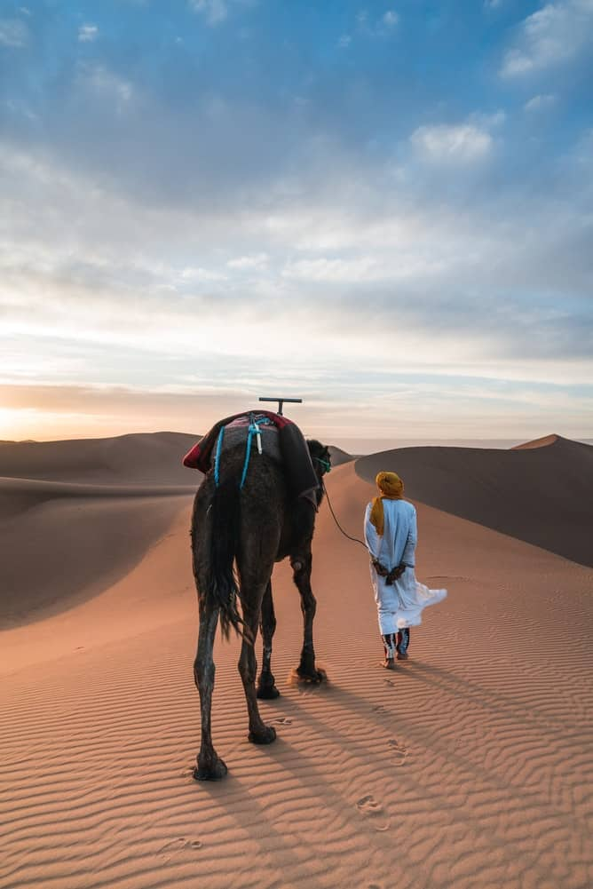 A man walking with a camel in the desert
