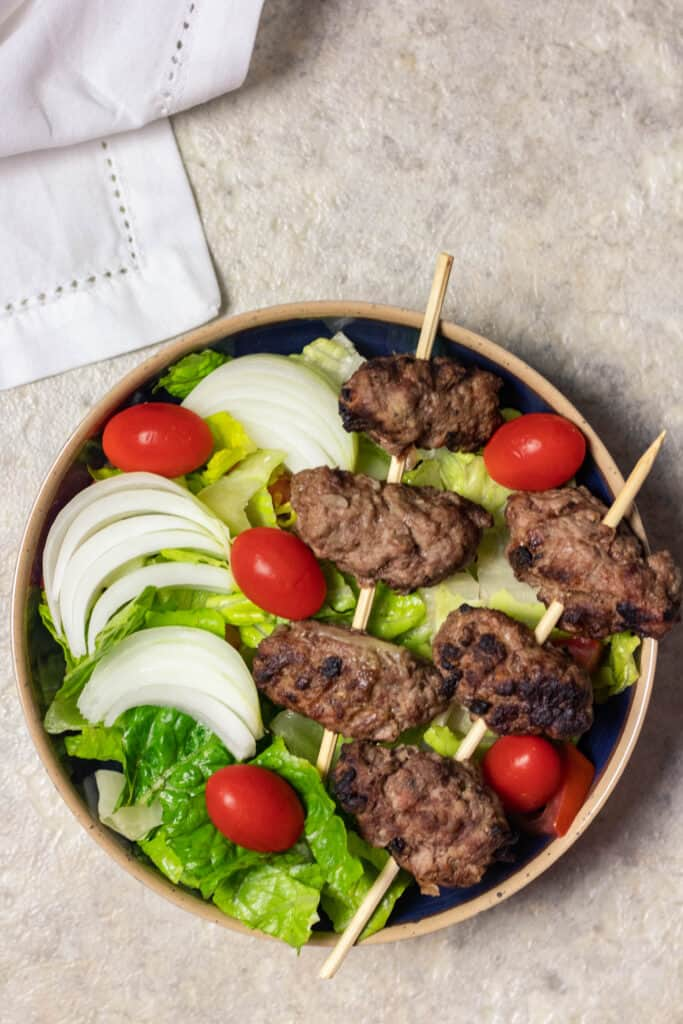 Bowl of cevapi on skewers over lettuce and tomatoes