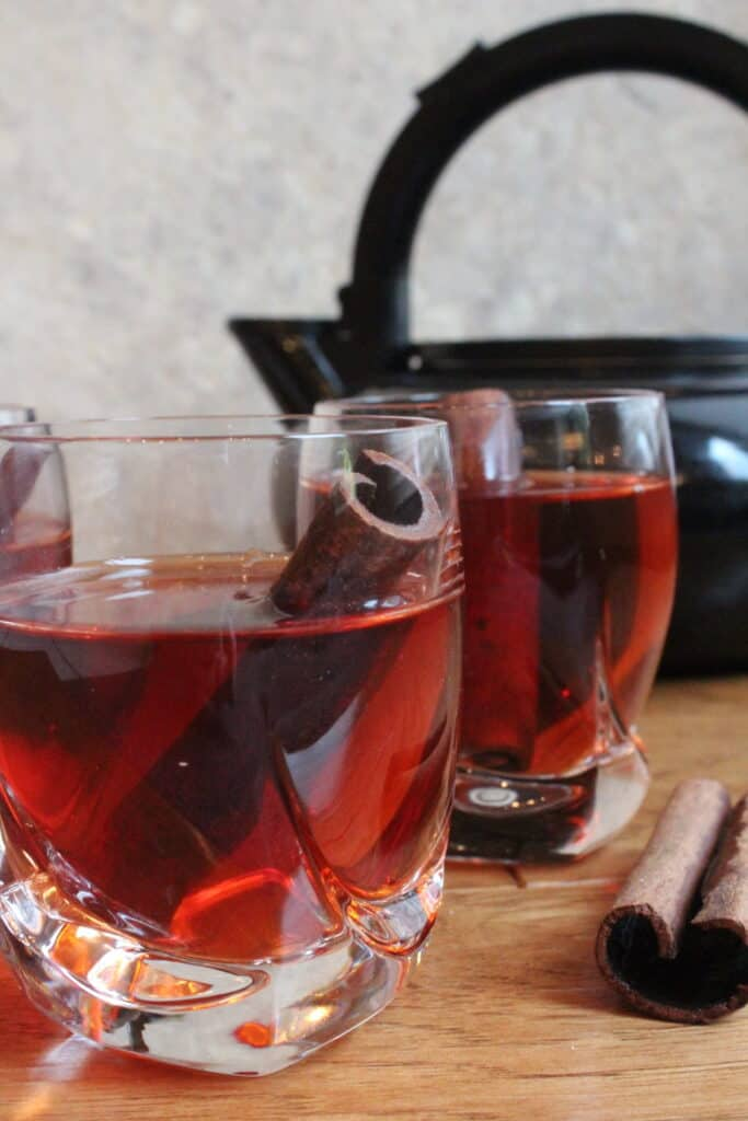 Front view of two glasses of cinnamon tea with a tea pot in the background