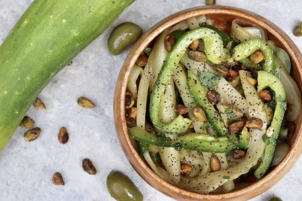Overhead view of cucumber salad with pistachios and olives