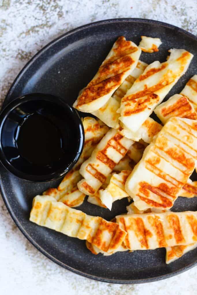 Overhead view of grilled halloumi with a side of honey