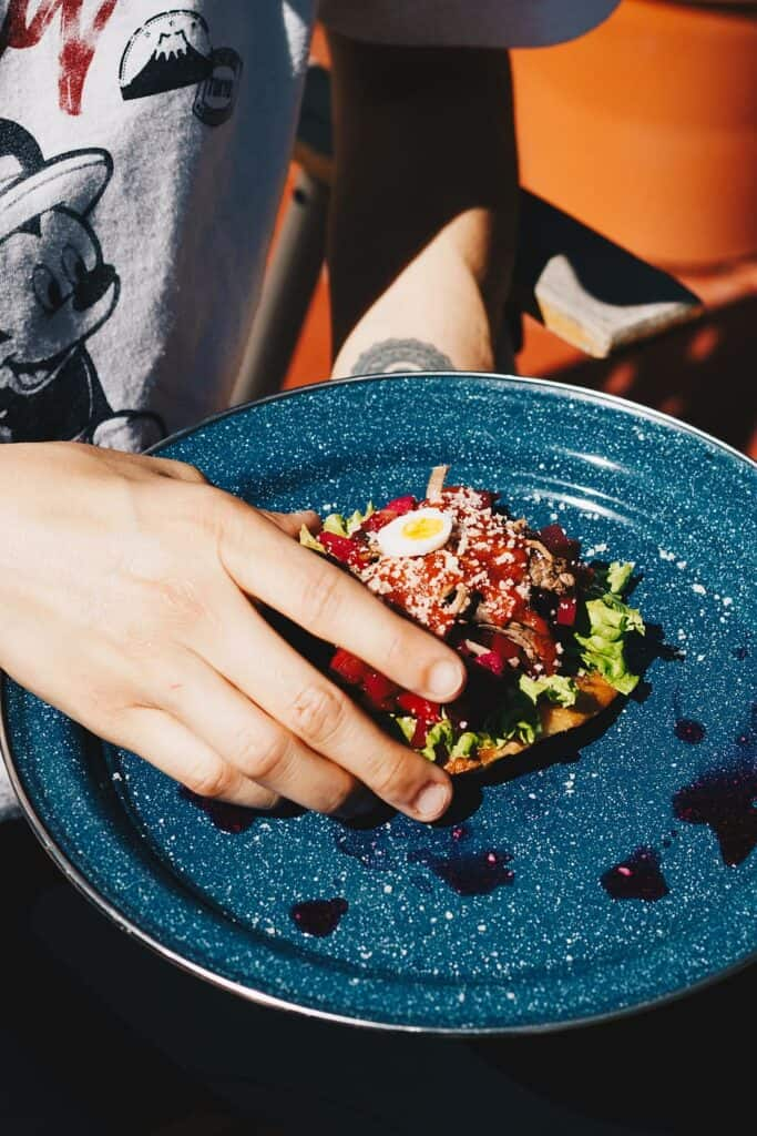 A hand picking a tostada off of a blue plate