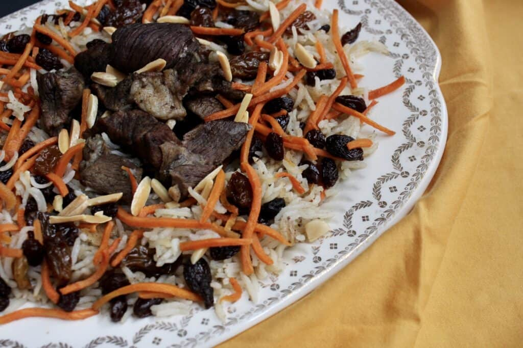 Front view of Kabuli pulao on a yellow napkin sprinkled with shredded carrots and raisins