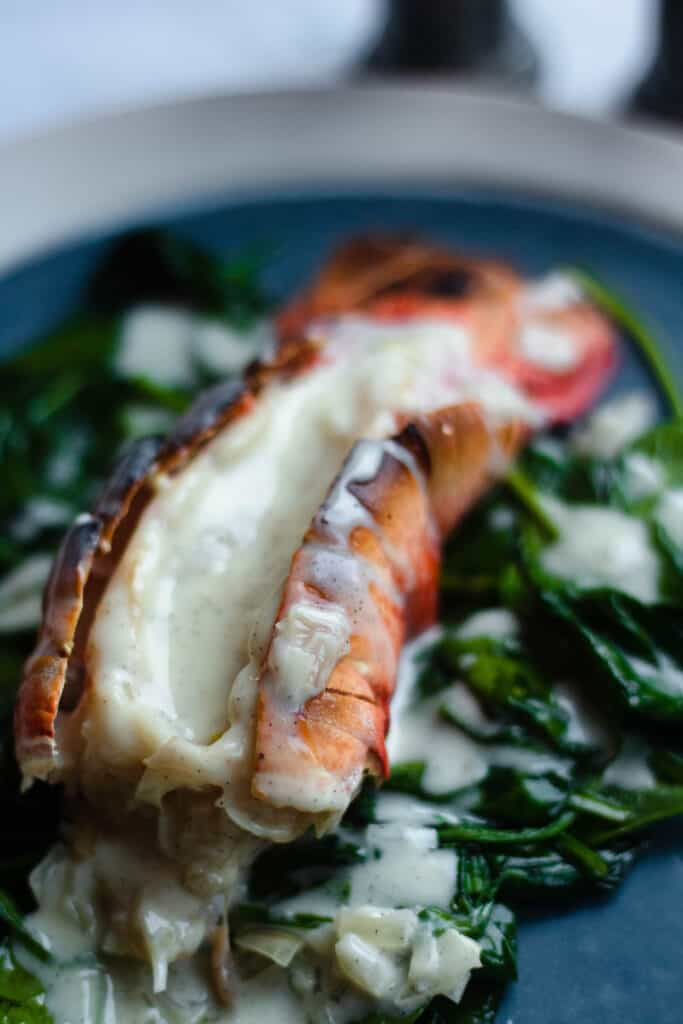 Lobster tail covered in vanilla sauce on sauteed spinach