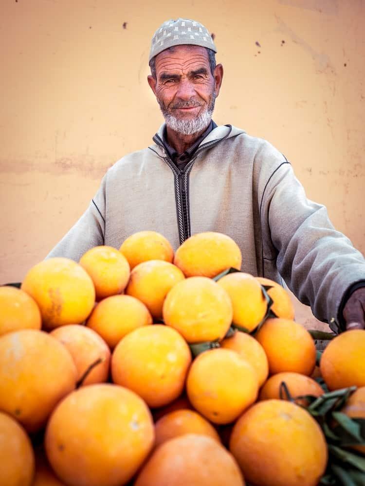 A Moroccan man serving oranges