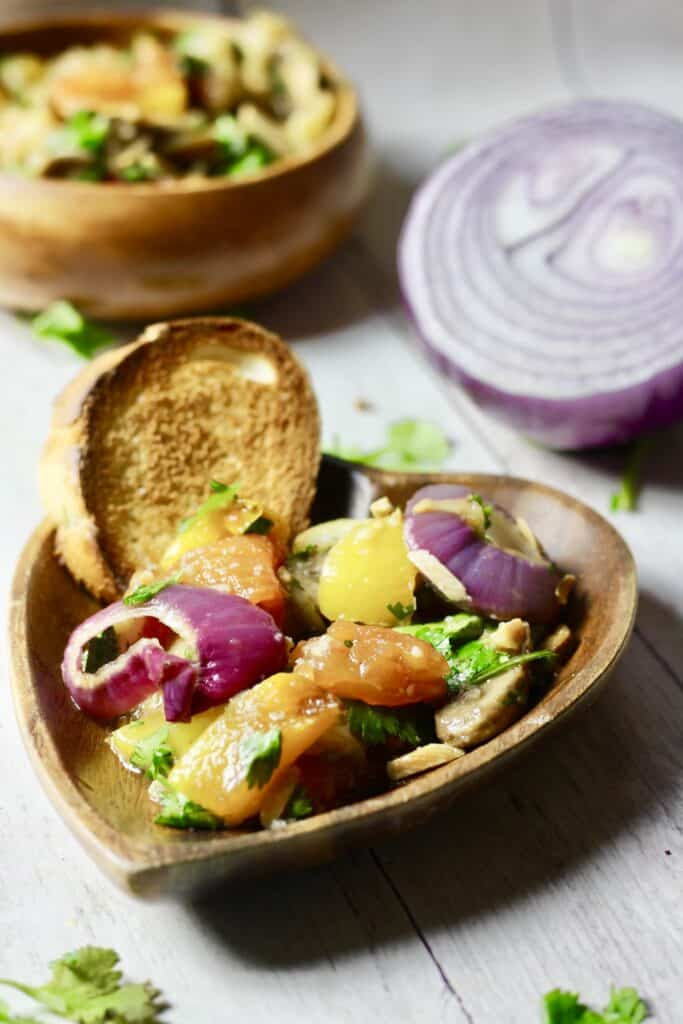 Mangal salad in a wooden, heart shaped dish and a slice of bread