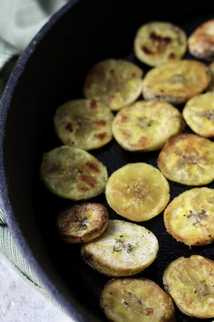 Cast iron skillet filled with plantain chips, close up view