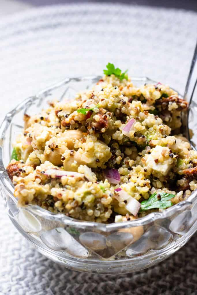 Glass bowl with quinoa salad and spoon sticking out