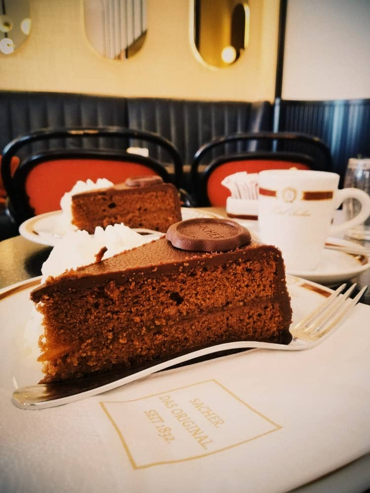 Plate of sacher torte cake with fork, coffee, and sacher-labeled napkin