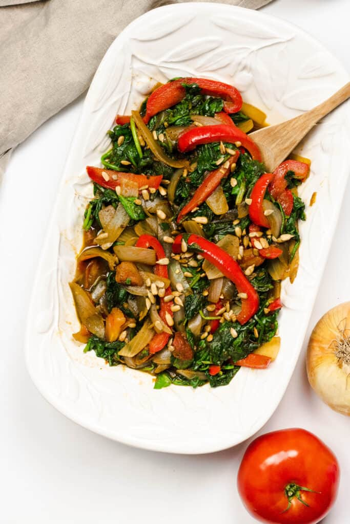 Bowl of Sauteed spinach from Botswana with red peppers and mushrooms