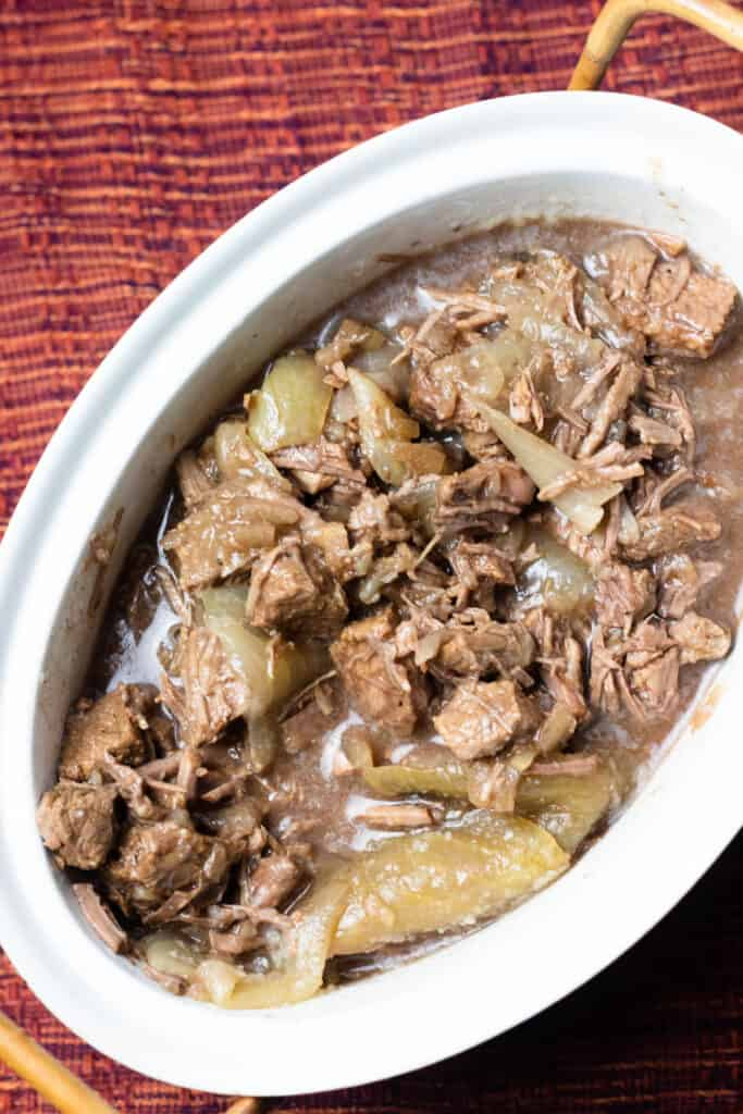 Oval container of beef stew with onions