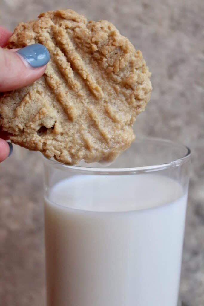 Hand dipping tahini cookie in milk