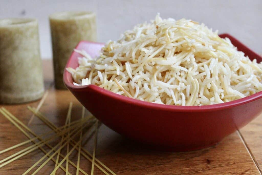 Horizontal view of red bowl filled with rice and vermicelli noodles