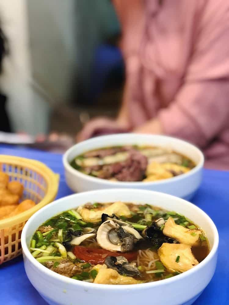 Two bowls of soup with mushrooms and green onions