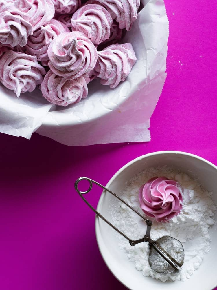 Bright magenta background with homemade marshmallows and powdered sugar