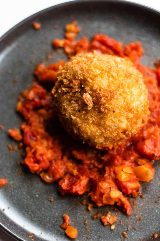 Risotto ball sitting on red sauce