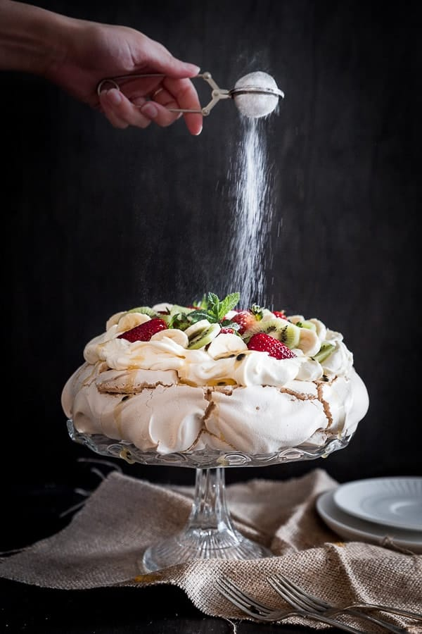 Pavlova on a black background with kiwi and strawberries and being sprinkled with sugar