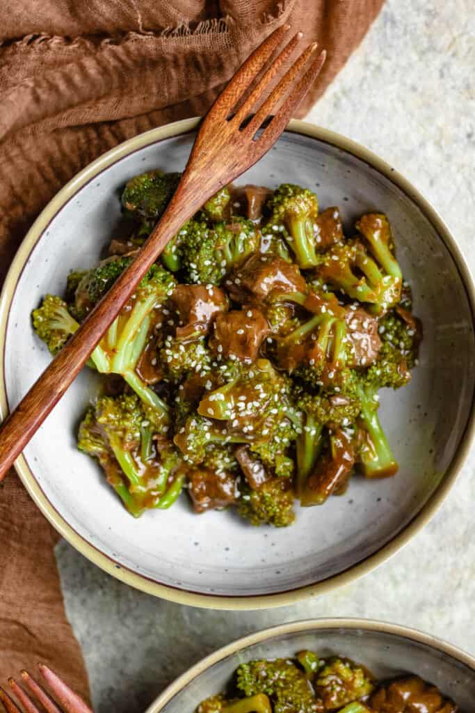 Close up of bowl with beef and broccoli and wooden spoon
