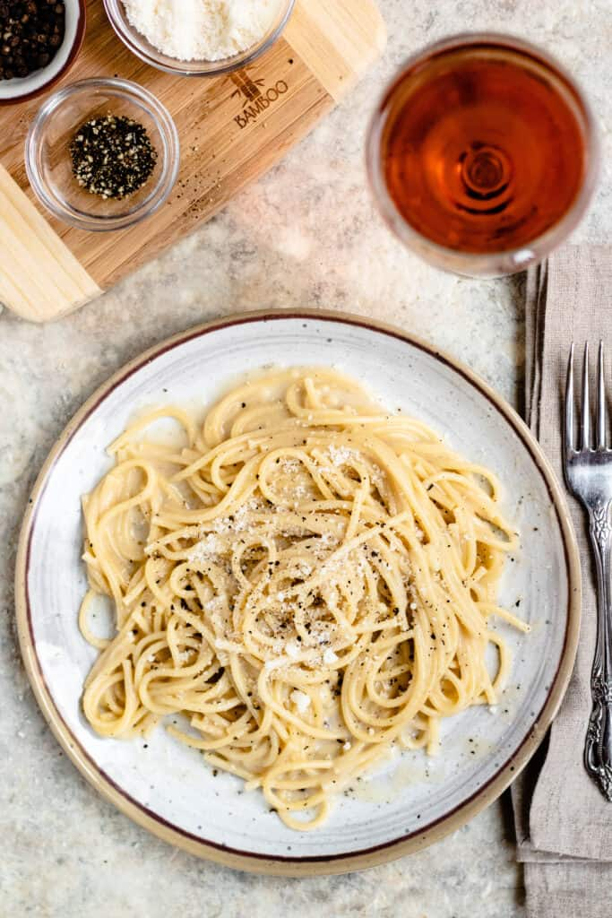 Overhead view of Cacio e pepe on a white place with place setting